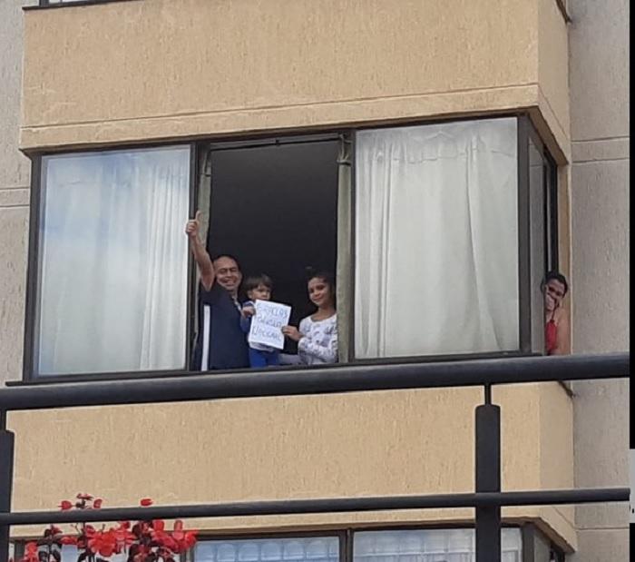 Personas agradeciendo desde las ventanas