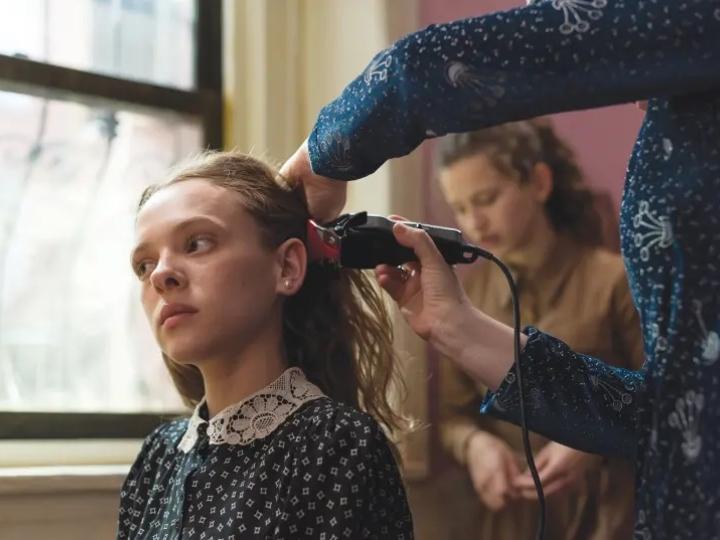 Escena de la serie Poco ortodoxa, Esty cortando su cabello a a rapa para llevar peluca
