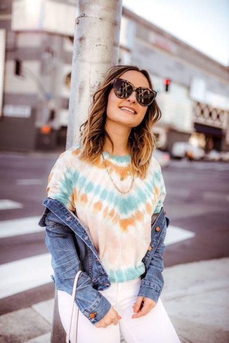 Chica con cabello suelto y lentes usa chaqueta de mezclilla y blusa con efecto deslavado o tie dye