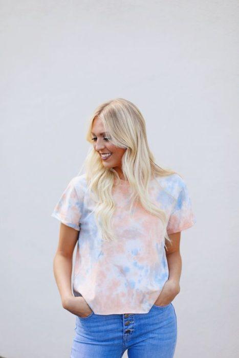 Mujer rubia con cabello suelto posa en una pared blanca con una blusa tie dye en color pastel