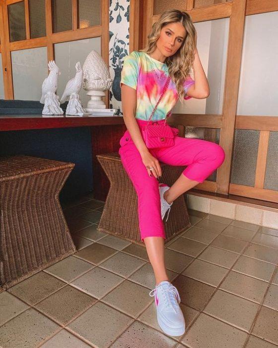 Chica rubia apoya su cabeza en la mano mientras viste pantalón rosa y una blusa tie dye