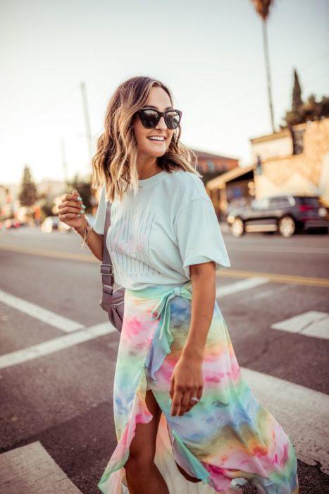 Chica con cabello suelto con ondas usa gafas de sol, blusa azul y falda tie dye