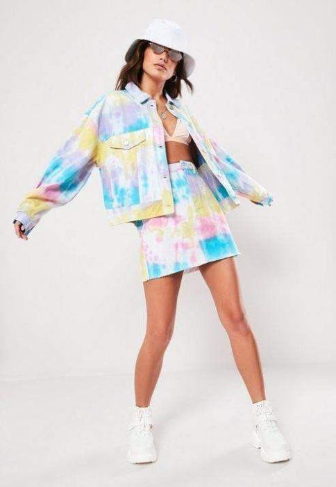 Modelo morena usa chaqueta y falda de mezclilla decoloradas en color azul, morado y amarillo