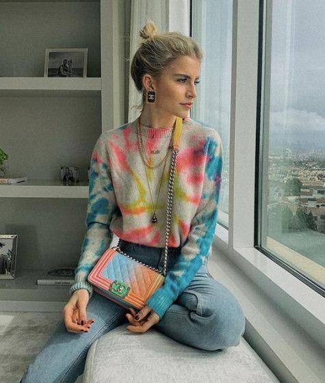 Chica rubia sentada en una ventana usa suéter con efecto tie dye