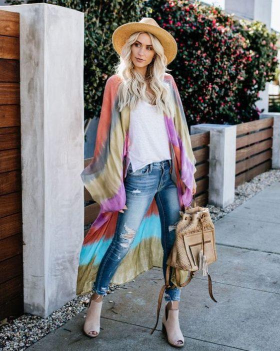 Chica rubia posa de pie con un sombrero y un kimono tie dye