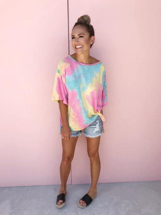 Chica sonrié y usa blusa con efecto tie dye sobre pared color rosa
