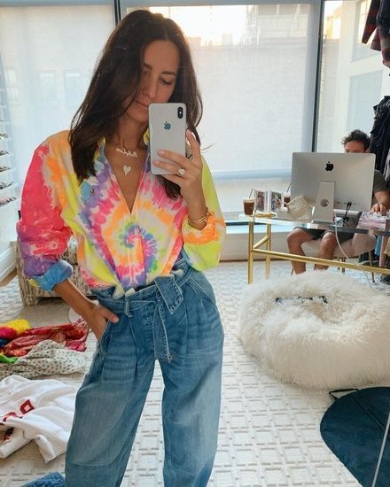 Chica se toma selfie en su habitación con jeans y una playera con efecto tie dye
