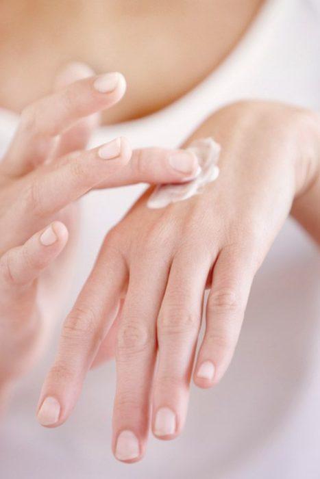 Mujer aplicando crema en sus manos