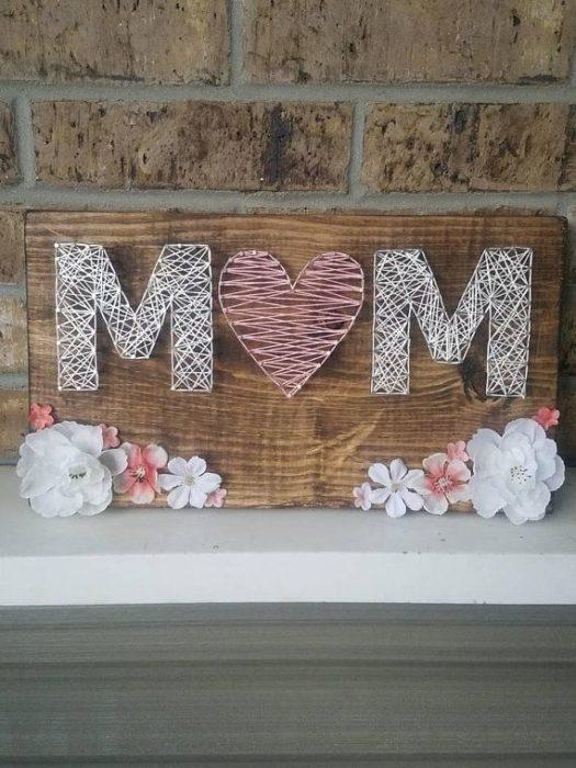 tabla con clavos e hilo que forman la palabra mamá