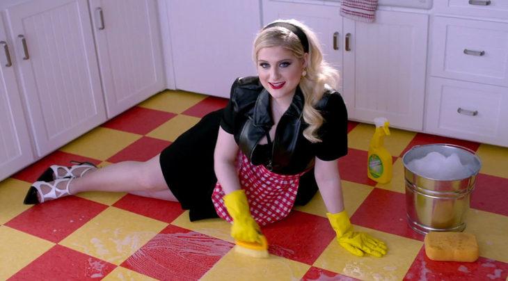 Chica recostada en el suelo limpiando con un cepillo y guantes