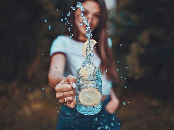 Chica sosteniendo un vaso de agua con rodajas de limón