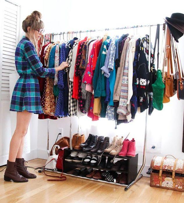 Chica viendo la ropa que tiene colgada