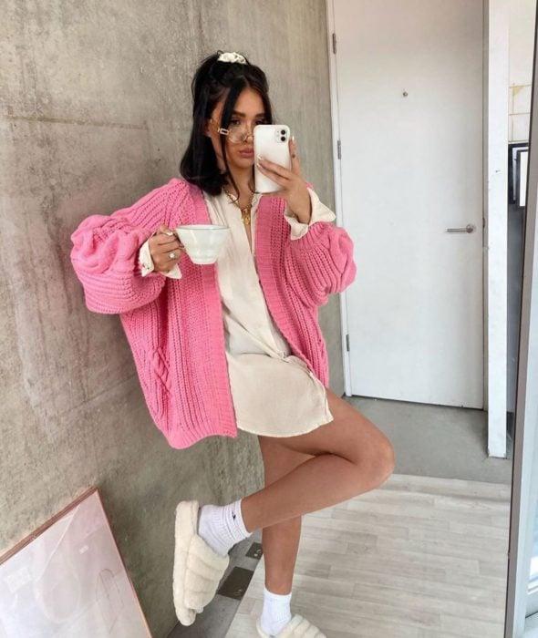 Chica usando suéter holgado color rosa