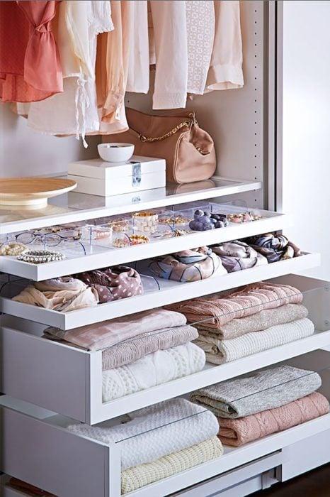Cajones de armario con cardigans doblados