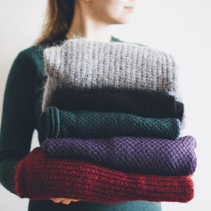 Chica cargando suéteres doblados