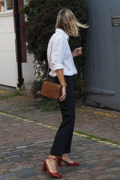 Mujer posa de espalda y usa blua blanca, jeans negros y tacones cuadrados