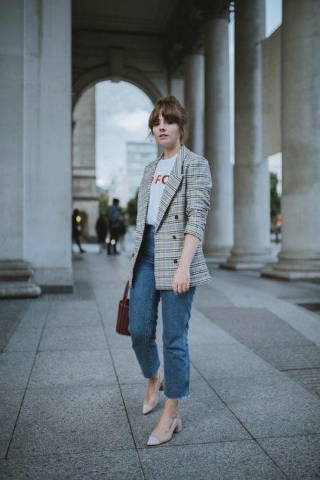 Mujer con saco café de cuadros viste jeans y zapatos beige con tacón cuadrado