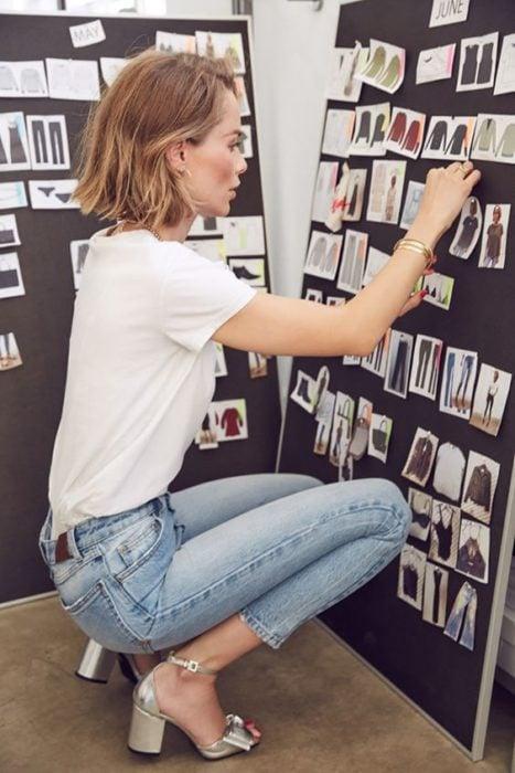 Mujer de cabello corto agachada pegando fotos usan jeans pantalón de mezclilla y tacones cuadrados color plata