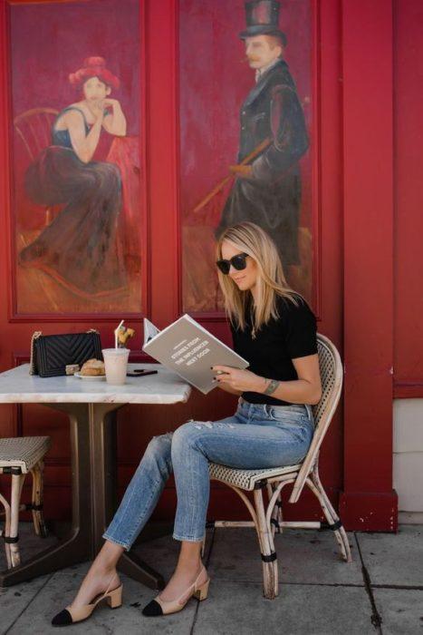 Mujer rubia sentada leyando la carta de un restaurante viste blusa negra, jeans, lentes de sol y zapatos cuadrados