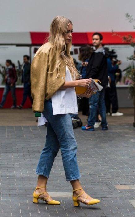 Mujer con cabellosuelto viste jeans, chaqueta dorada tacones cuadrados