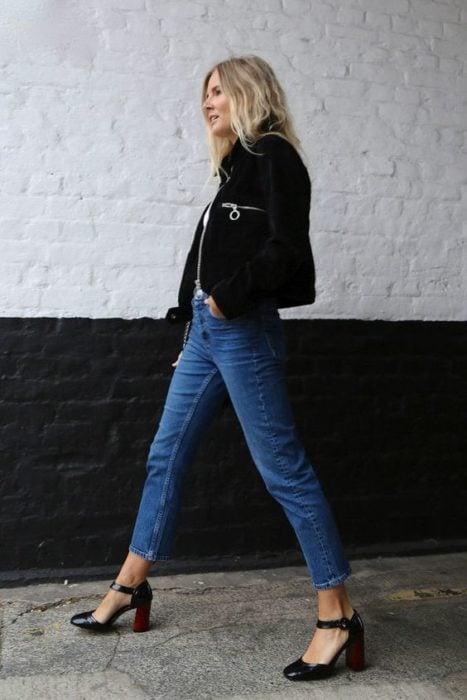 Chica rubia de cabello suelto con chaqueta negra, pantalón de mezclila y tacones cuadrados