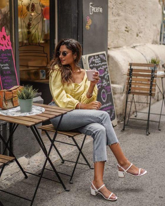 Mujer sentada cruza la pierna y viste blusa amarilla, pantalón gris y tacones blancos cuadrados