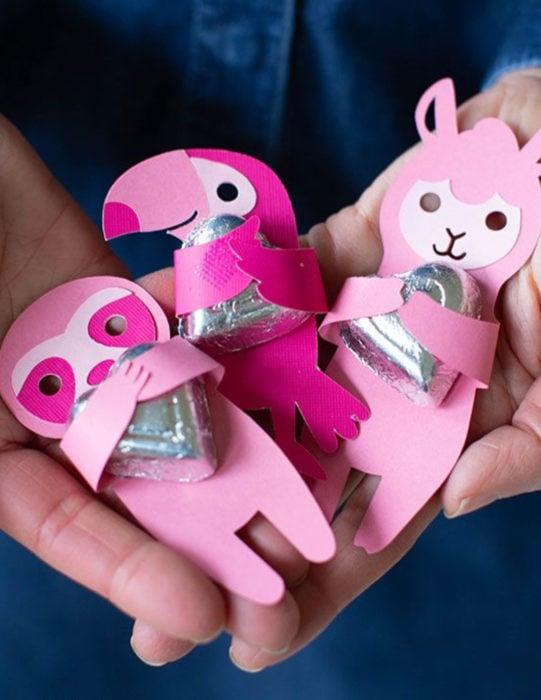 Tarjetas de felicitación infantiles para el Día del Niño; animales rosas de papel con chocolates, llama,, tucán, oso perezoso