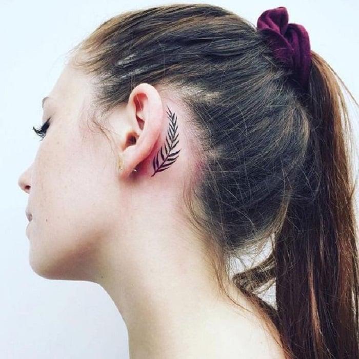 Tatuaje detrás de la oreja de una hoja de palmera