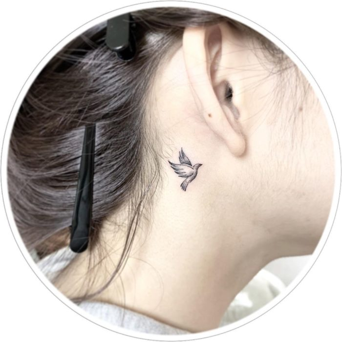 Tatuaje detrás de la oreja de una golondrina