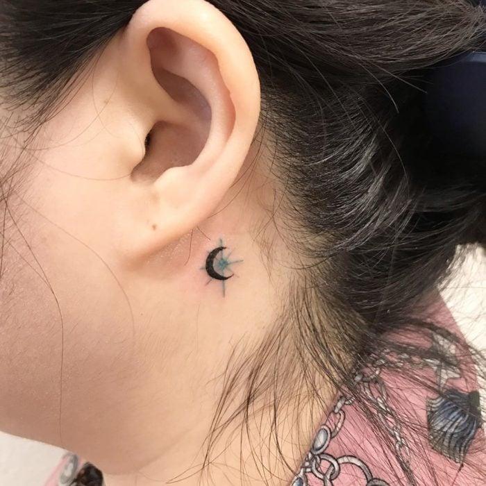 Tatuaje detrás de la oreja de la luna y la estrella de oriente