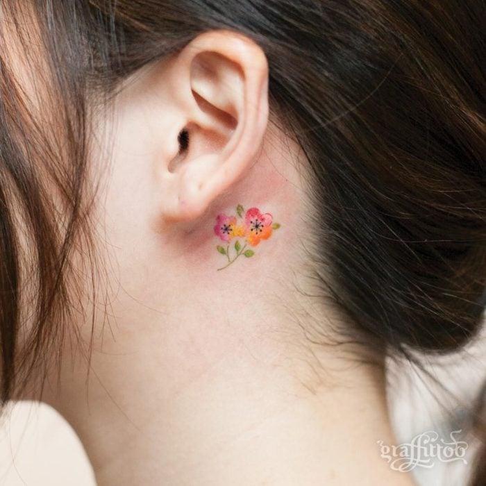 Tatuaje detrás de la oreja de ramito de flores
