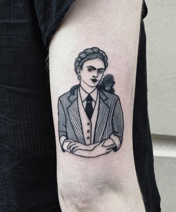 Tatuajes de Frida Kahlo con traje y mono, en el brazo