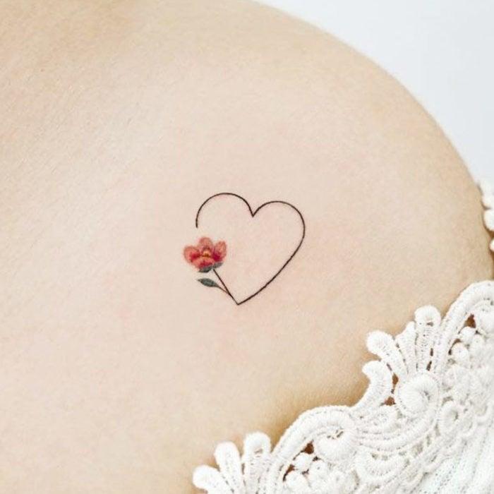 Tatuajes para regalarle a mamá el 10 de mayo; corazón con flor minimalista