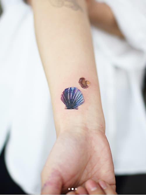 Chica con un tatuaje en forma de concha de mar con un pez