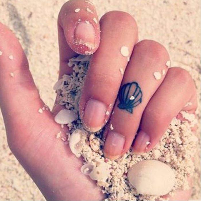 Chica con un tatuaje en forma de concha de mar en un dedo