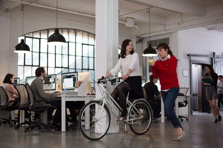 Escena de la película Pasante de moda, cuando Jules va en bicileta en el pasillo del trabajo