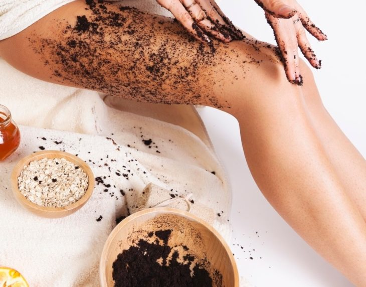 Girl applying coffee and oatmeal mask on legs to remove cellulite