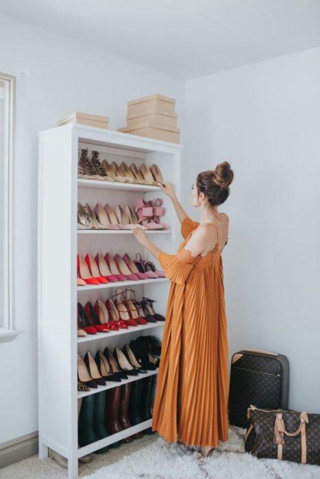 Mujer con vestido naranja acomoda zapatos en una mueble blanco