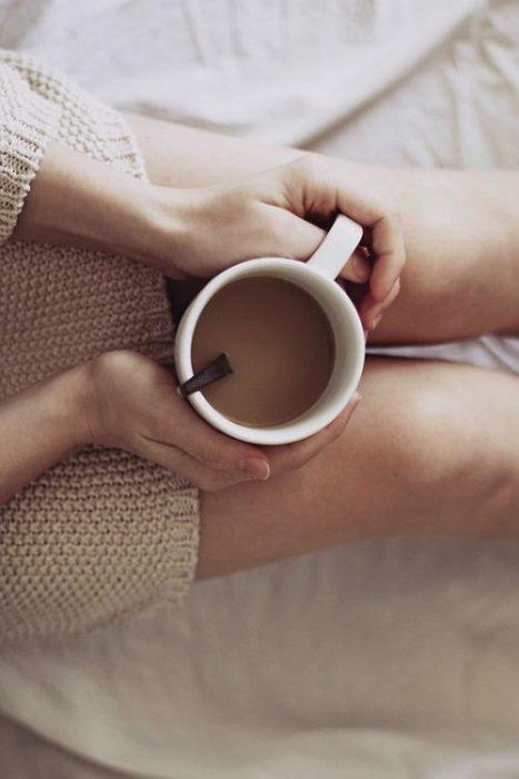 Chica sosteniendo una taza de café entre las piernas