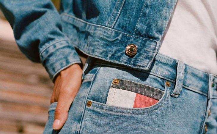 Mujer usando jeans y cazadora Tommy hecha con materiales 100 por ciento reciclados