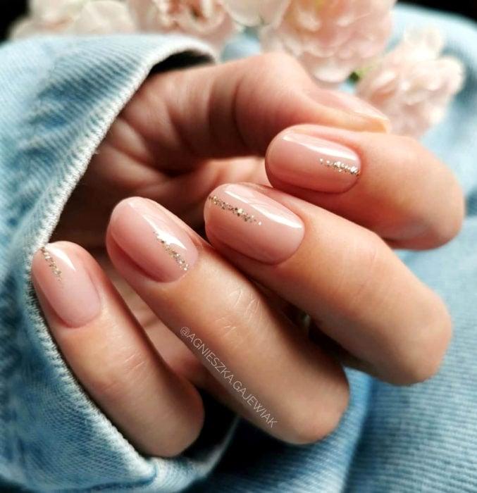 Diseños de uñas sencillos para hacer en casa; esmalte nude con glitter