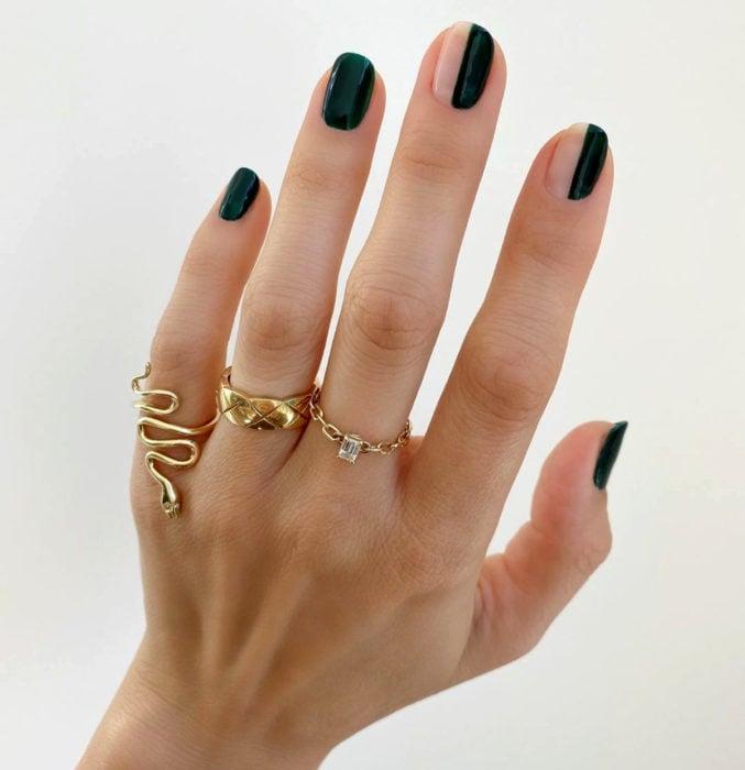 Diseños de uñas sencillos para hacer en casa; esmale verde oscuro, líneas verticales, mano con anillos dorados de serpiente