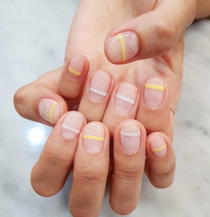 Diseños de uñas sencillos para hacer en casa; líneas horizontales con esmalte blanco y amarillo