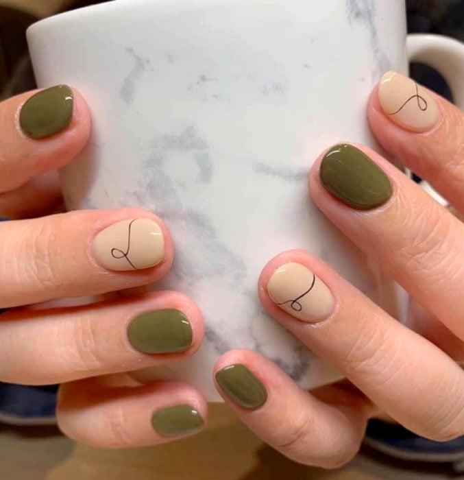 Diseños de uñas sencillos para hacer en casa; esmalte nude, verde con líneas curvas