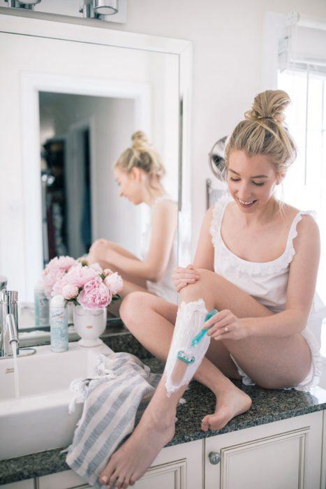 Chica depilando sus piernas en el baño