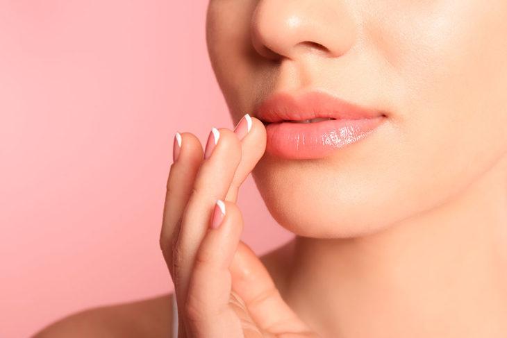 Chica humectando sus labios con aceite para bebé