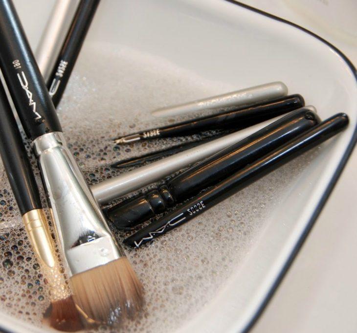Brochas de maquillaje dentro de un tazón con agua y jabón