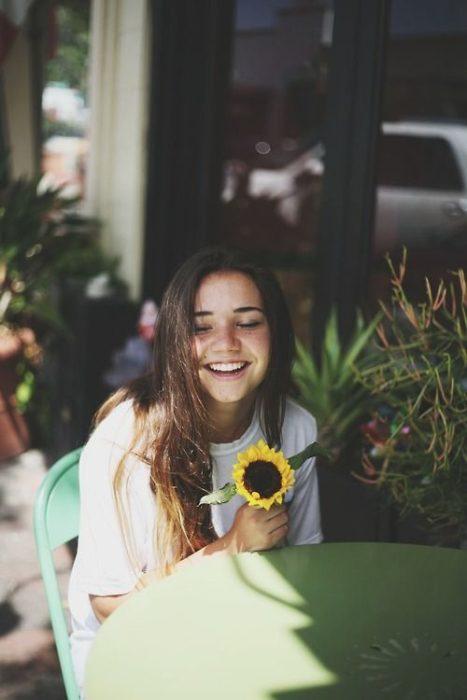 Chica sonriendo csosteniendo un girasol en la mano