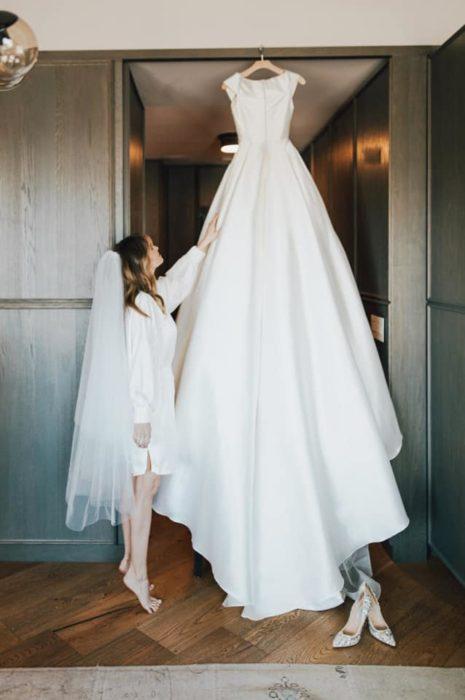 Debby Ryan posando junto a su vestido de boda blanco con diseño plisado