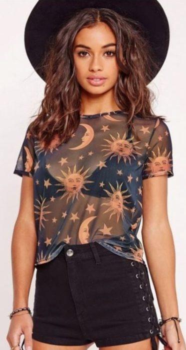 Chica usandobralette negro con blusa de transparencia de lunas y estrellas